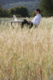 Businessman using laptop at table in rural field Royalty Free Stock Photography