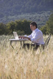 Businessman using laptop at table in rural field Royalty Free Stock Photos