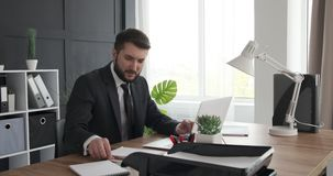 Businessman using laptop and taking notes. Businessman reading email on laptop and taking down notes at office desk stock video
