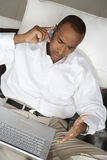 Businessman Using Laptop And Talking On Cellphone Stock Photography