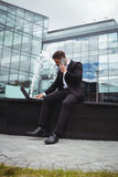 Businessman using laptop while talking on phone. In office building Royalty Free Stock Images