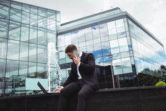 Businessman using laptop while talking on phone. In office building Royalty Free Stock Photo