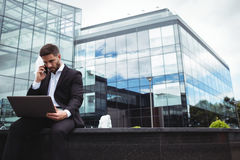 Businessman using laptop while talking on phone. In office building Stock Image