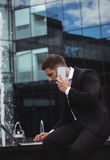 Businessman using laptop while talking on phone. In office building Stock Photo
