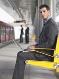 Businessman Using Laptop At Train Station Stock Photo
