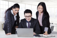 Businessman using laptop with two subordinates Royalty Free Stock Photo