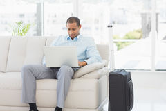 Businessman using laptop waiting to depart on business trip Royalty Free Stock Photography
