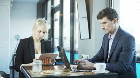 Businessman is Using Laptop, Woman is Using Tablet stock video footage