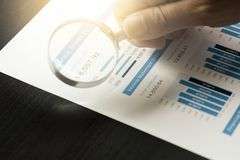 Businessman using magnifier glass  for financial data analysis and find the best company from stock market.
