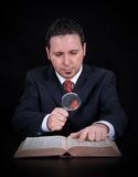 Businessman is using the magnifying glass Stock Images