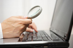 Businessman is using  magnifying glass   Royalty Free Stock Images