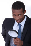 Businessman using magnifying glass Stock Photography