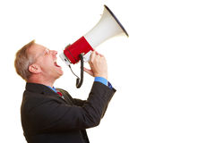 Businessman using a megaphone. Senior businessman screaming loudly in a big megaphone Stock Photos