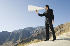 Businessman Using Megaphone in Desert Stock Photo
