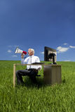 Businessman Using Megaphone In A Field. Business concept shot of a man sitting at a desk using a megaphone in a green field with a bright blue sky. Shot on Royalty Free Stock Photos