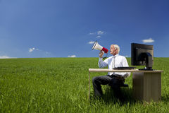 Businessman Using Megaphone In A Field. Business concept shot of a man sitting at a desk using a megaphone in a green field with a bright blue sky. Shot on Royalty Free Stock Photo