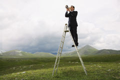 Businessman Using Megaphone In Mountain Field Stock Photo