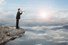 Businessman using megaphone yelling on cliff with sunlight cloud. Scape background Royalty Free Stock Photos