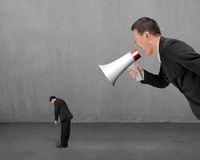 Businessman using megaphone yelling at his employee with concret. E room background Stock Images