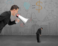 Businessman using megaphone yelling at his employee with doodles. Wall background Royalty Free Stock Image