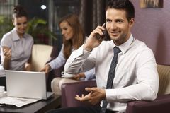 Businessman using mobile at hotel lobby Royalty Free Stock Images