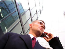 Businessman using a mobile phone. Standing outside a modern office building Royalty Free Stock Photography