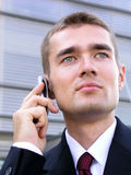 Businessman using a mobile phone. Standing outside a modern office building Stock Photography