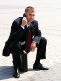 Businessman using a mobile phone. Sitting on a briefcase Royalty Free Stock Image