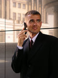 Businessman using a mobile phone. Standing outside a modern office building Royalty Free Stock Images