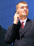 Businessman using a mobile phone. Standing outside a modern office building Stock Photo