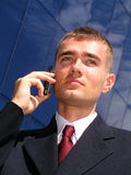 Businessman using a mobile phone. Standing outside a modern office building Royalty Free Stock Photo