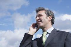 Businessman Using Mobile Phone Against Cloudy Sky Stock Photos
