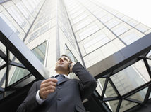 Businessman Using Mobile Phone Against Tall Office Building Royalty Free Stock Photo
