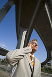 Businessman using mobile phone beneath overpasses, low angle view Stock Photo