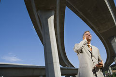 Businessman using mobile phone beneath overpasses, low angle view Stock Images