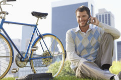 Businessman Using Mobile Phone By Bicycle In Park Royalty Free Stock Photos