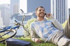 Businessman Using Mobile Phone By Bicycle In Park Royalty Free Stock Image