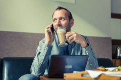Businessman using mobile phone during breakfast at home/hotel. I. Ndoor photo Stock Photography