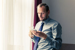 Businessman using mobile phone during breakfast at home/hotel. I. Ndoor photo Stock Images