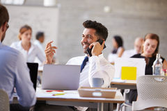 Businessman Using Mobile Phone In Busy Office Royalty Free Stock Images
