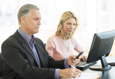 Businessman Using Mobile Phone While Colleague Working At Desk Stock Photo