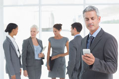 Businessman using mobile phone with colleagues behind Royalty Free Stock Photos