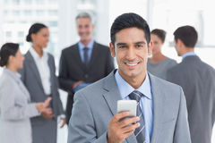 Businessman using mobile phone with colleagues behind Stock Photos