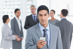Businessman using mobile phone with colleagues behind Stock Photo