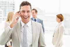 Businessman using mobile phone with colleagues behind Royalty Free Stock Photography