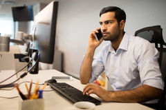 Businessman using mobile phone and computer in office. Young businessman talking on mobile phone while using computer in office Stock Photo