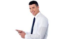 Businessman using mobile phone. Corporate guy sending message through mobile phone Stock Photos