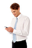 Businessman using mobile phone. Corporate guy sending text messages Royalty Free Stock Photography