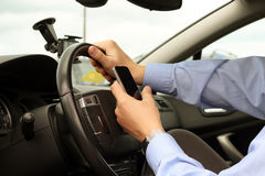 Businessman using  mobile  phone while driving the car Stock Photos