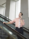 Businessman Using Mobile Phone On Escalator Royalty Free Stock Photo